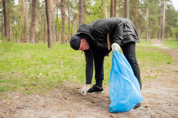Man volunteer collecting garbage in park stock photo