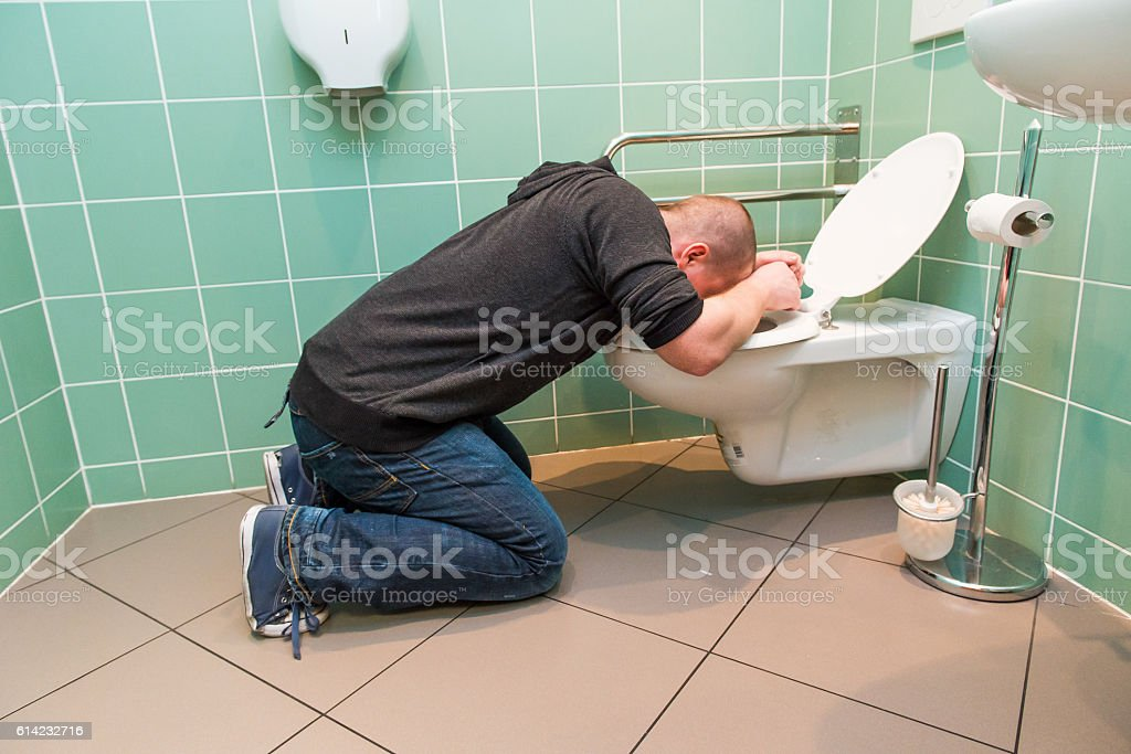 man vomiting in the toilet stock photo