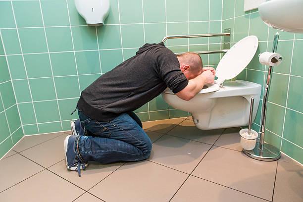 man vomiting in the toilet - kotze stock-fotos und bilder