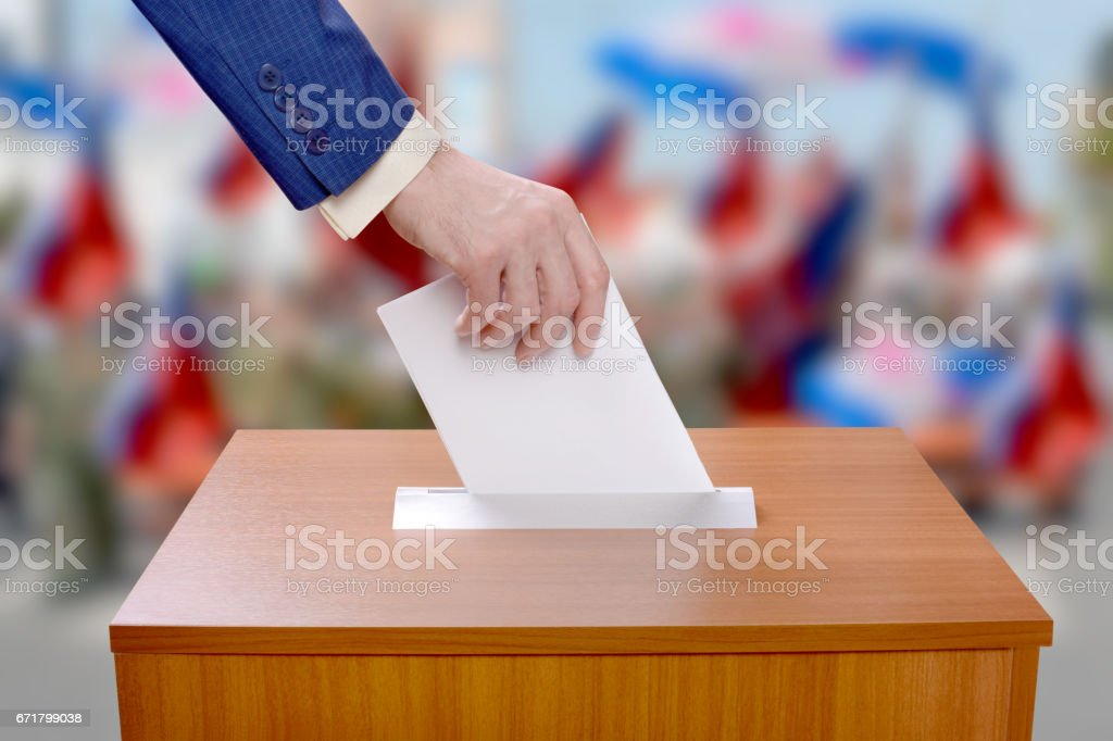 Man votes by throwing a ballot in the ballot box stock photo