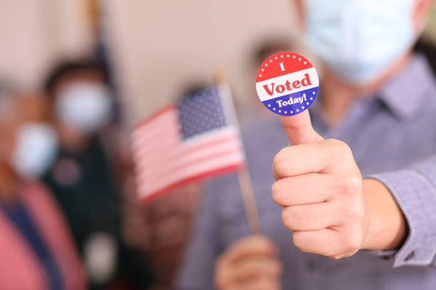 """Man votes in USA election wearing mask and I Voted sticker. Mature adult man votes in the USA election wearing a protective mask to protect against COVID-19 or other infectious diseases.  He shows off his """"I Voted"""" sticker. covid-19 stock pictures, royalty-free photos & images"""