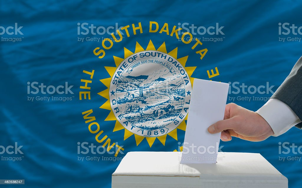 man voting on elections in front  flag of south dakota stock photo