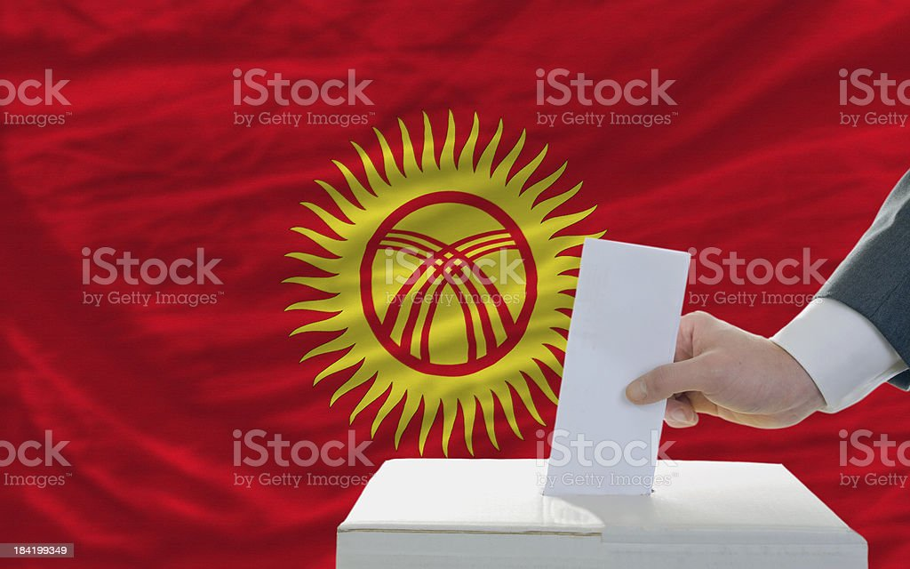 man voting on elections in kyrghyzstan front of flag royalty-free stock photo