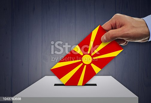 935056316 istock photo Man voting on elections in MACEDONIA front of flag 1043760558