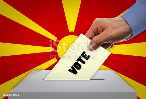935056316 istock photo Man voting on elections in MACEDONIA front of flag 1043760560