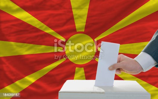 935056316 istock photo man voting on elections in macedonia front of flag 184059187