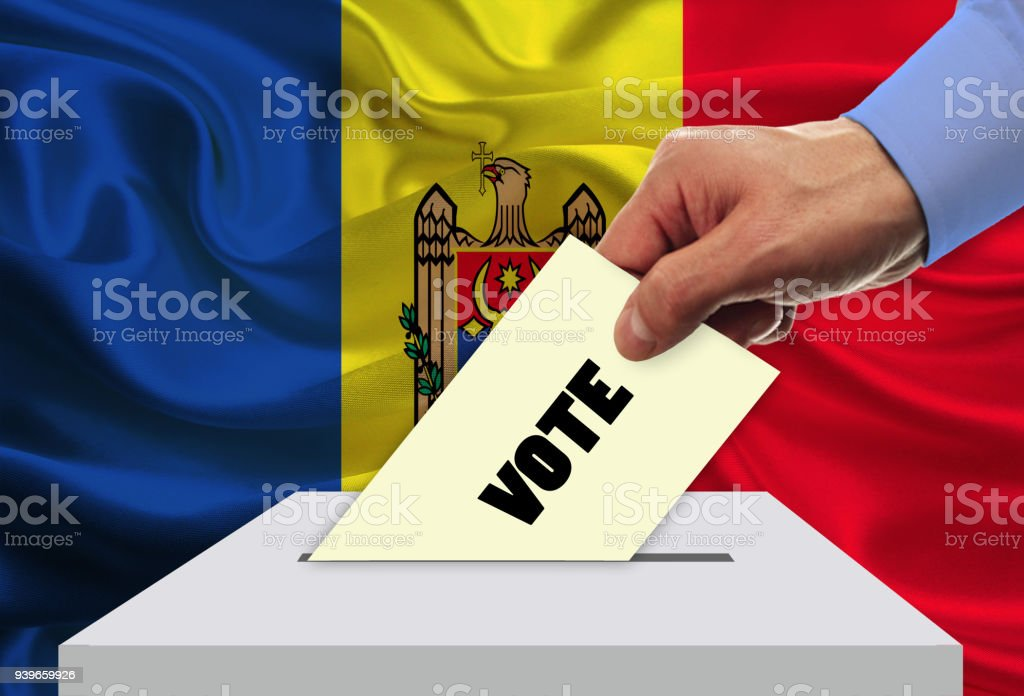 Man voting on elections in Moldova front of flag stock photo