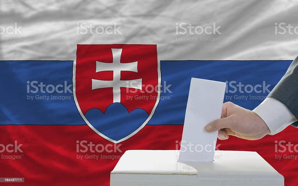 man voting on elections in slovakia front of flag royalty-free stock photo
