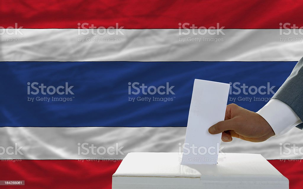 man voting on elections in thailand front of flag royalty-free stock photo