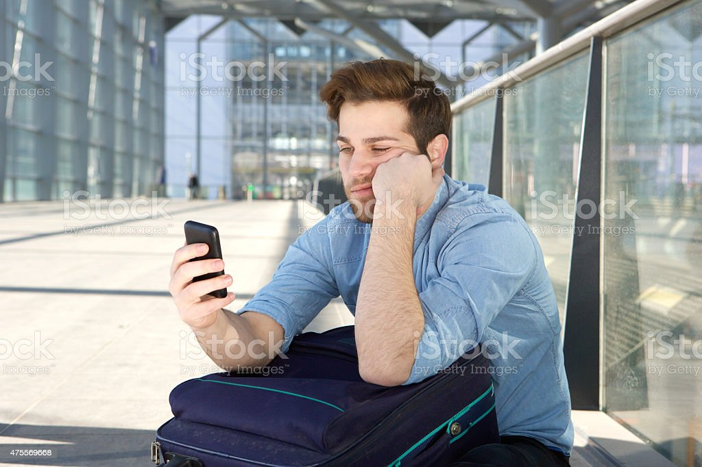 Man waiting at airport with bored expression on face stock photo