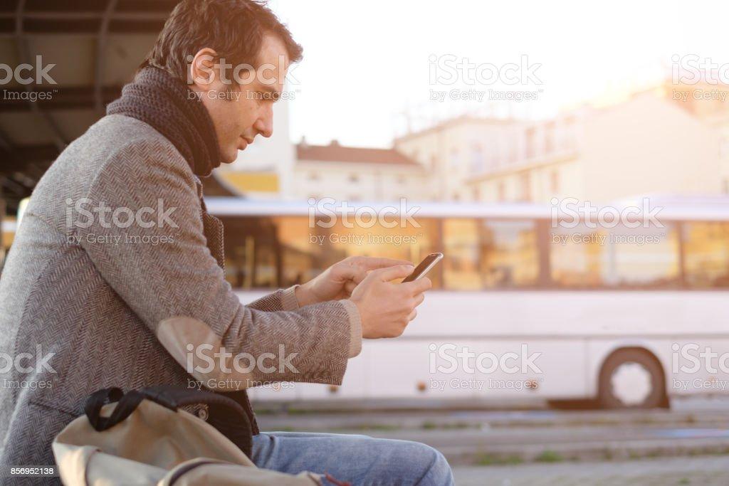Man waiting at the bus station and looking at his smart-phone - foto stock