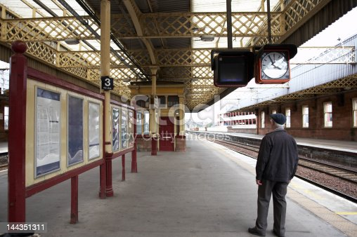 A man waiting for a train at the train station ( Paisley Gilmour Street), while looking up at the TV screen for up-to-date travel information. (which is blank)