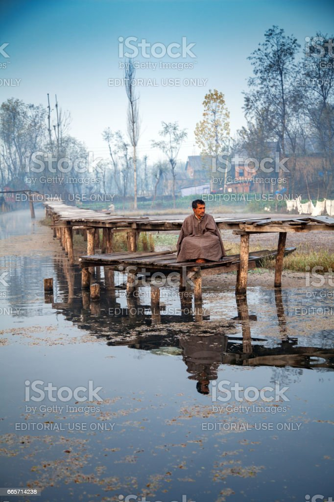 A man waiting for a ferrying boat at lakside of Dal lake stock photo