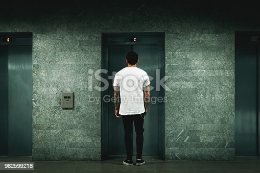638591126 istock photo Man waiting for elevator 962599218