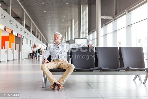 Mid adult man waiting for flight at the airport lounge. Businessman in casuals sitting on chair and waiting for plane.