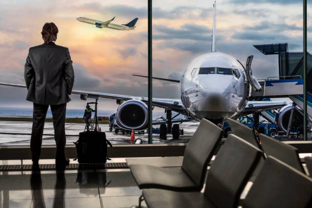 man waiting for flight in airport lounge - airport stock photos and pictures