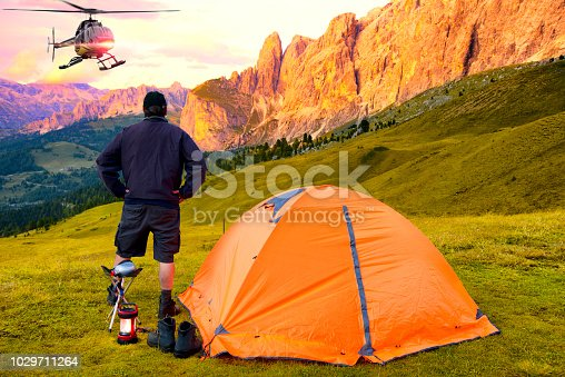Man waiting for helicopter rescue in mountain
