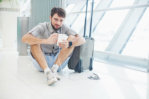 man waiting for his flight and speaking on his phone