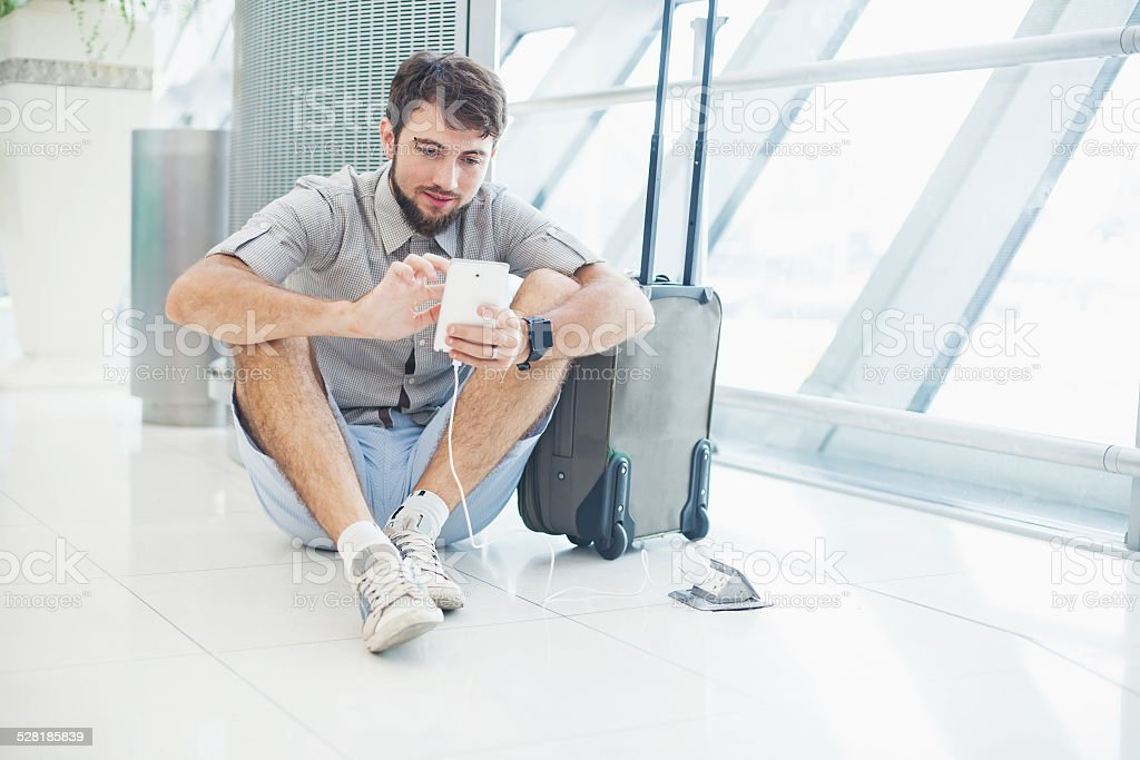 man waiting for his flight and speaking on his phone stock photo