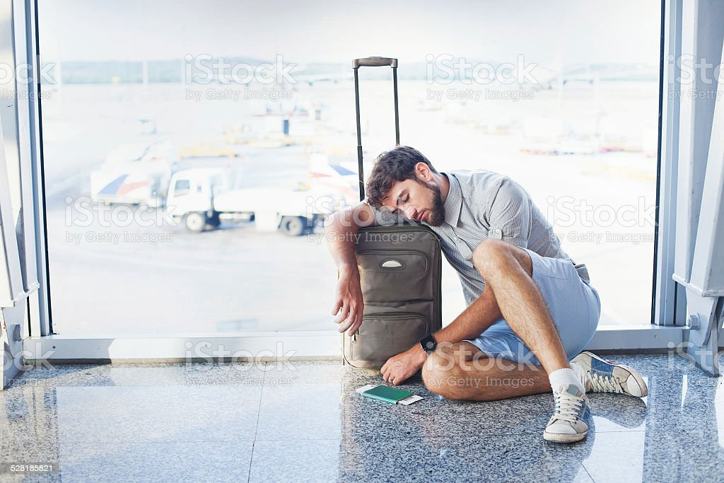 man waiting for his flight in the international airport stock photo