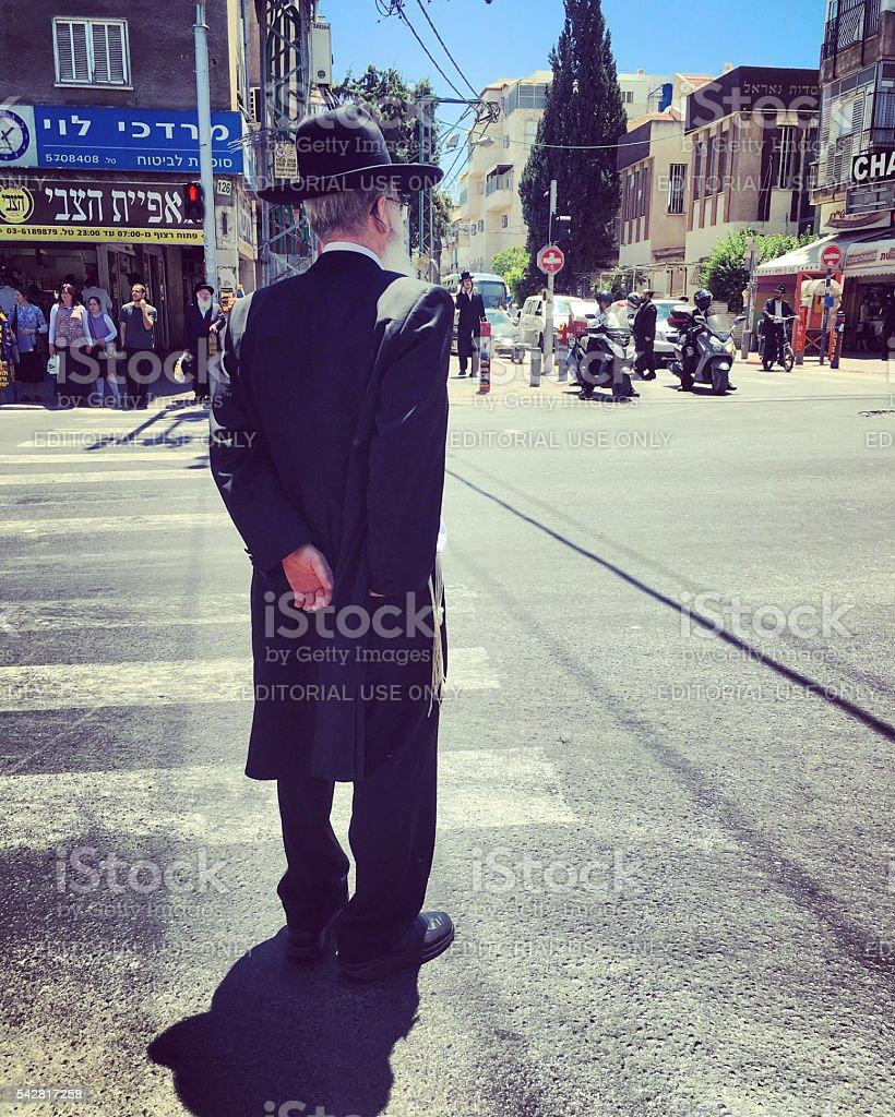 Man waiting to cross the street in Bnei Brak, Israel stock photo