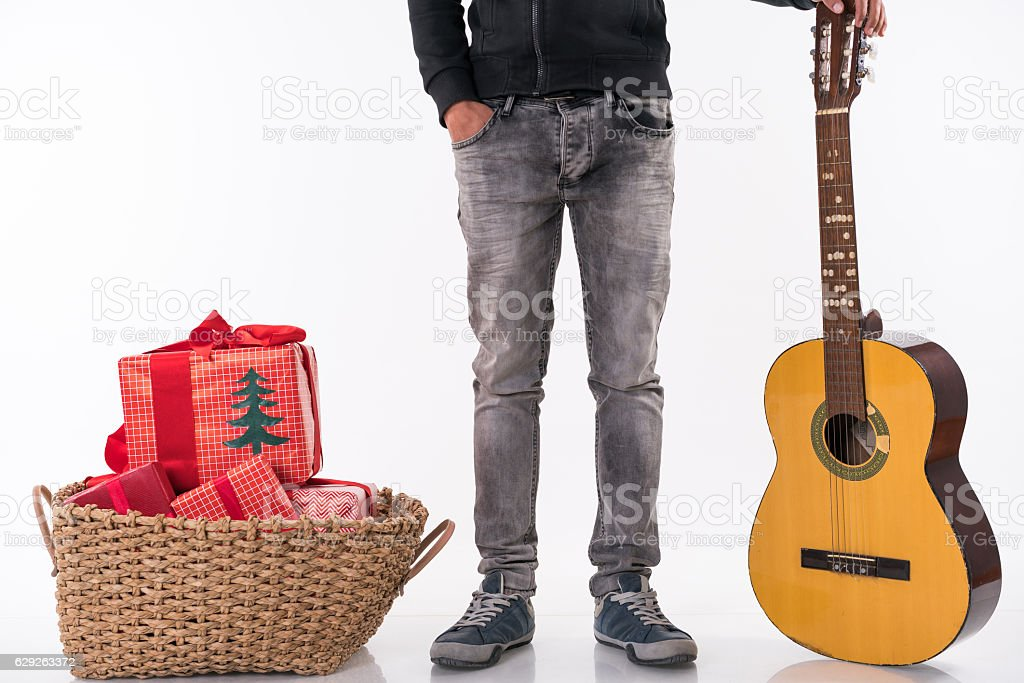 man waiting with Christmas gifts and classic  Guitar stock photo