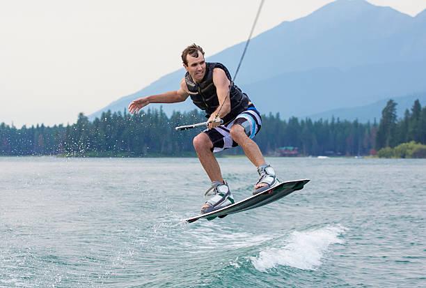 Man wakeboarding on a beautiful mountain lake stock photo