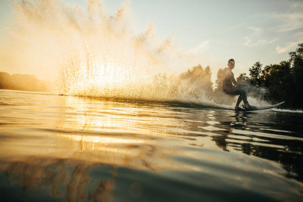 man wakeboarding on a lake - wassersport stock-fotos und bilder
