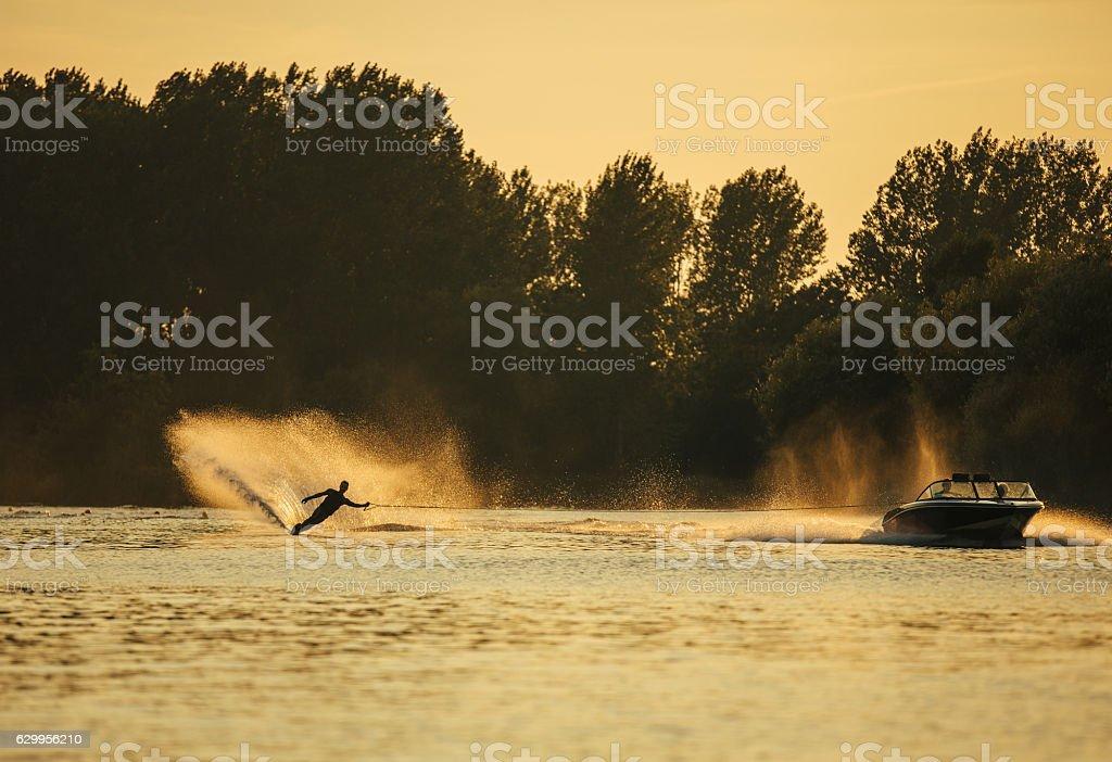Man wakeboarding on lake behind boat stock photo