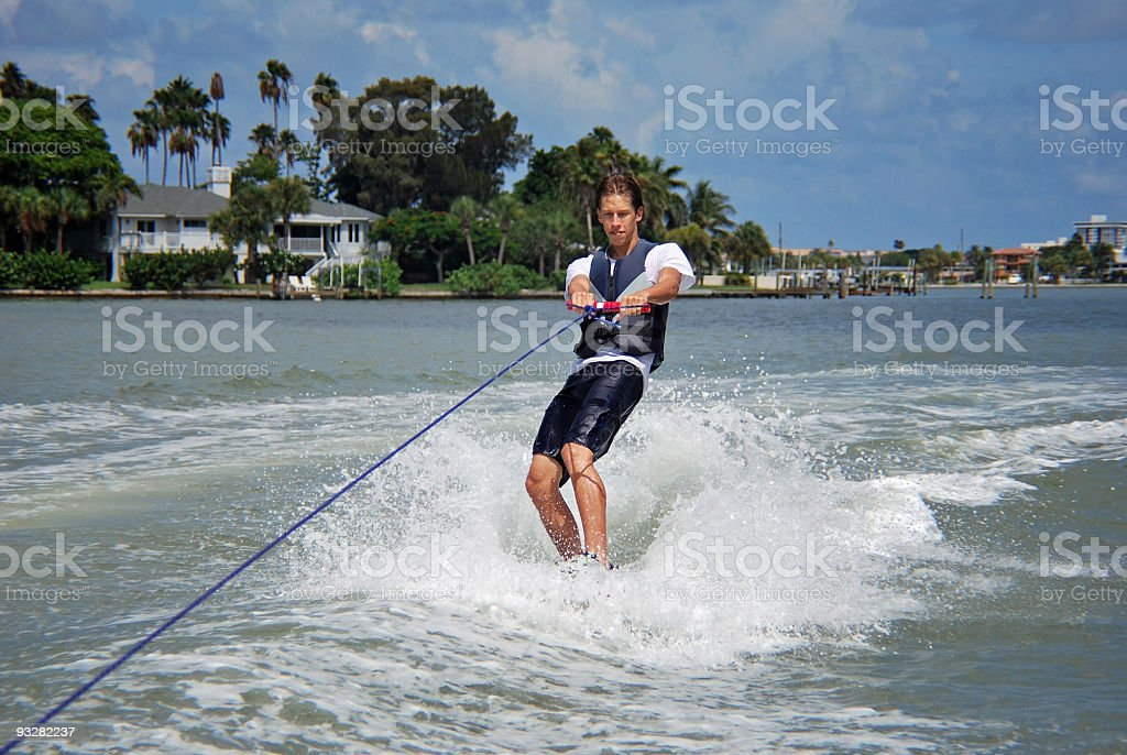 Man Wakeboarding with Background of Waterfront Home royalty-free stock photo