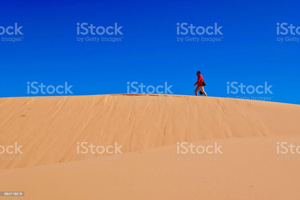 Man waking on sand dunes. stock photo
