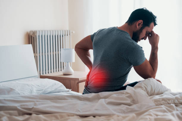 Man waking up in the morning and suffer for back pain stock photo