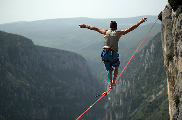 man walking a slackline over verdon gorges, france - balance stock pictures, royalty-free photos & images