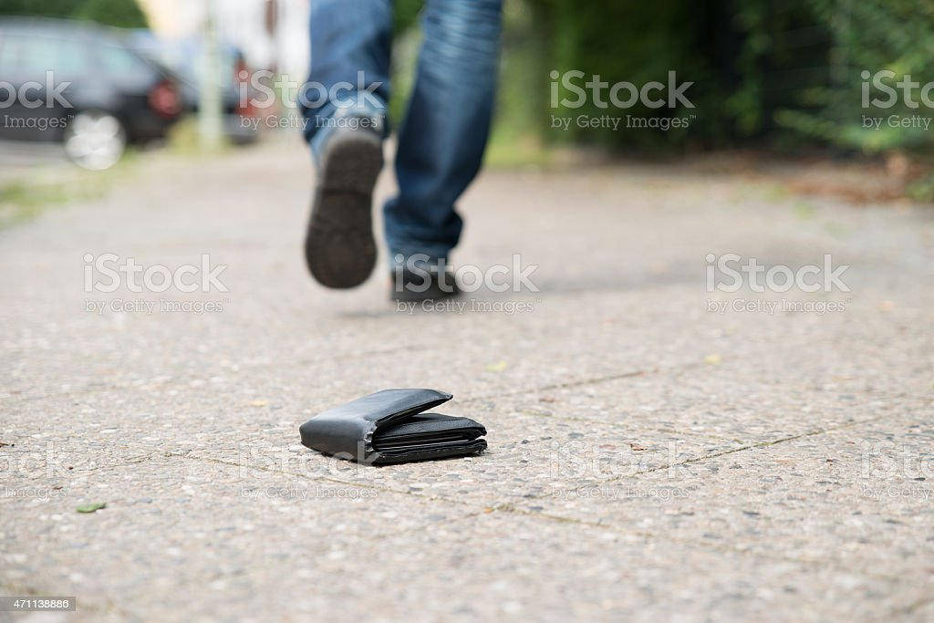 Man Walking Against Fallen Wallet On Street stock photo