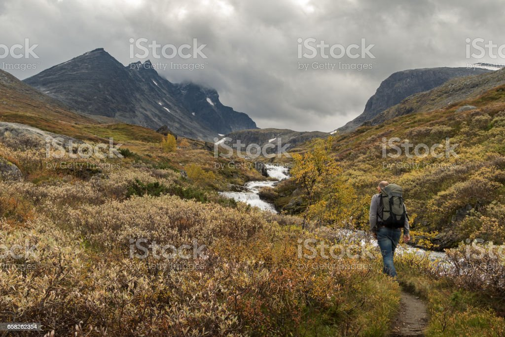 Man walking alone beside river stream towards the mountains of Hurrungane in Jotunheimen, Norway stock photo