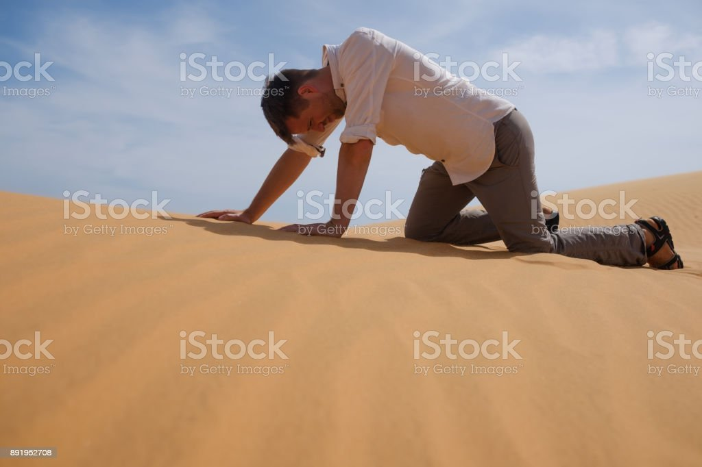 Man walking alone in the sunny desert. He is lost and out of breath. No water and energy. stock photo