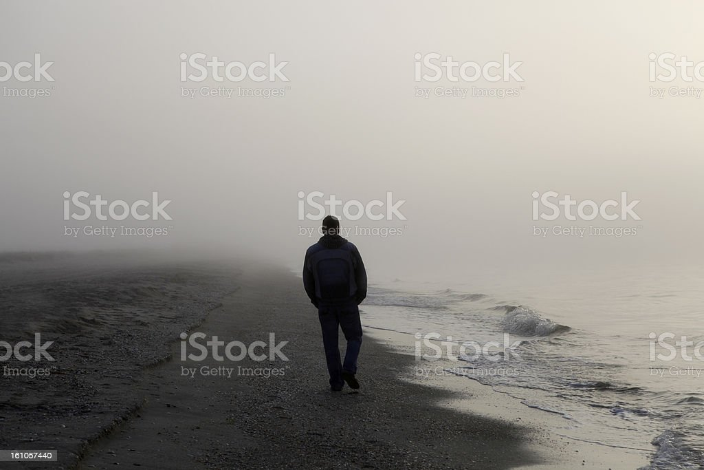 Man walking alone on a foggy beach stock photo