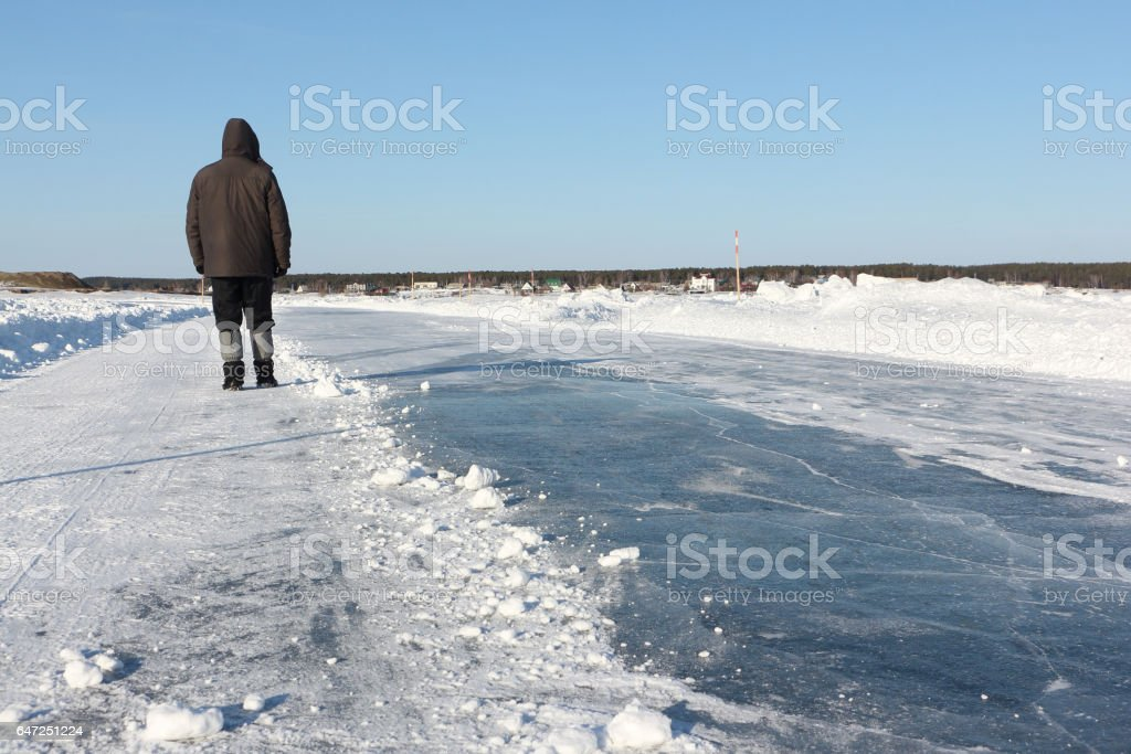 Man walking along a road of ice on the frozen reservoir in the winter stock photo