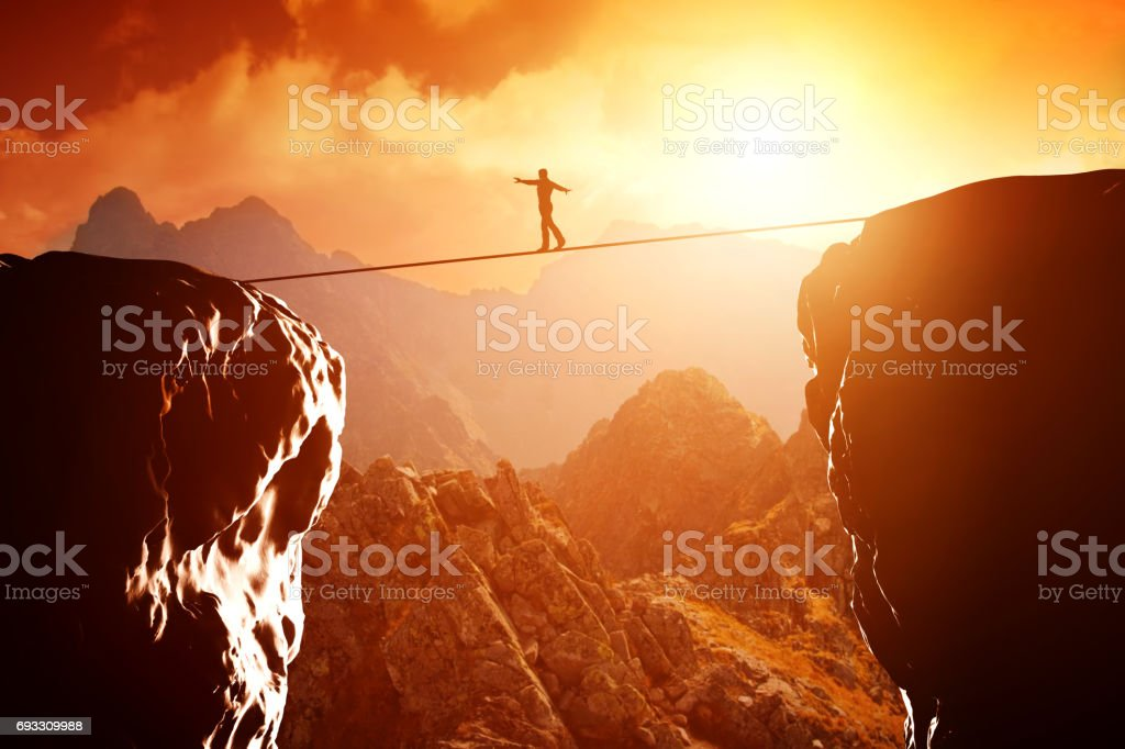 Man walking and balancing on rope over precipice in mountains at sunset stock photo