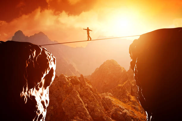 man walking and balancing on rope over precipice in mountains at sunset - balance stock pictures, royalty-free photos & images