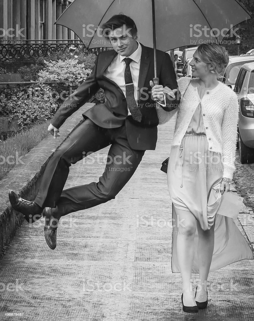 Man walking and jumping with umbrella girl by his side stock photo