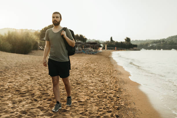 Man walking at the beach and carrying a backpack stock photo