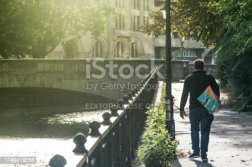 BERLIN, GERMANY - July 28, 2018: Man walking at the naturally beautiful environment near the pedestrian pass of the Spree river canal, with soft sunlight at the historical center of Berlin.