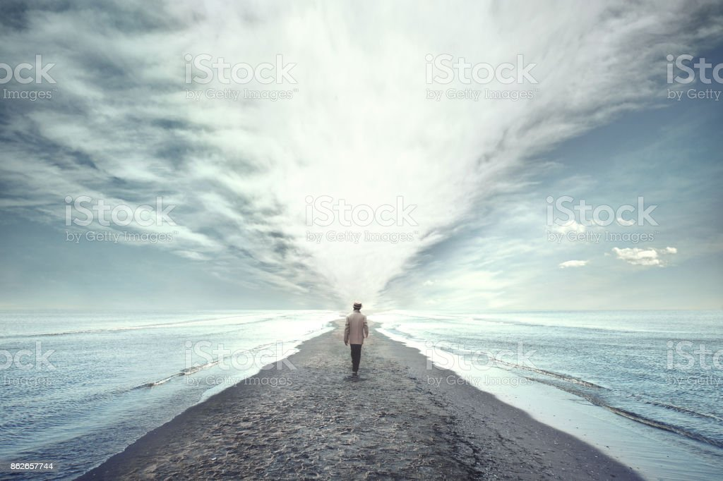 man walking between two seas - Zbiór zdjęć royalty-free (Abstrakcja)