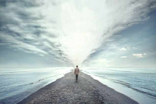 man walking between two seas - ethereal stock pictures, royalty-free photos & images