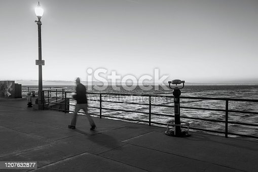Man walks on the Huntington Beach pier in the evening with coin-operated binoculars on the pier and distant oil platforms lit up at night. Slow shutter speed; tourist is unrecognizable due to motion blur. Catalina Island is seen on the horizon. The pier railings provide leading lines in this black and white photograph. Copy space.