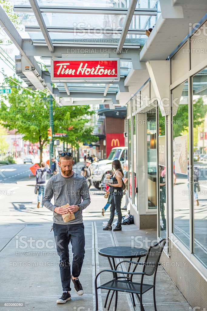Man walking by Tim Hortons restaurant with food in downtown stock photo