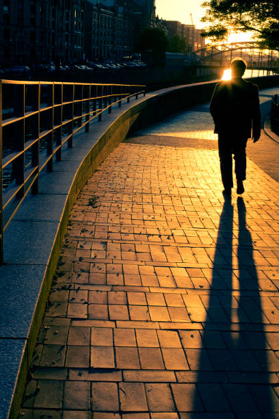 man walking down street at sunset - walking home sunset street bildbanksfoton och bilder