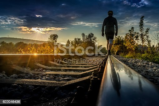 Man in a cycling outfit Walking Down the Rails to Sunset