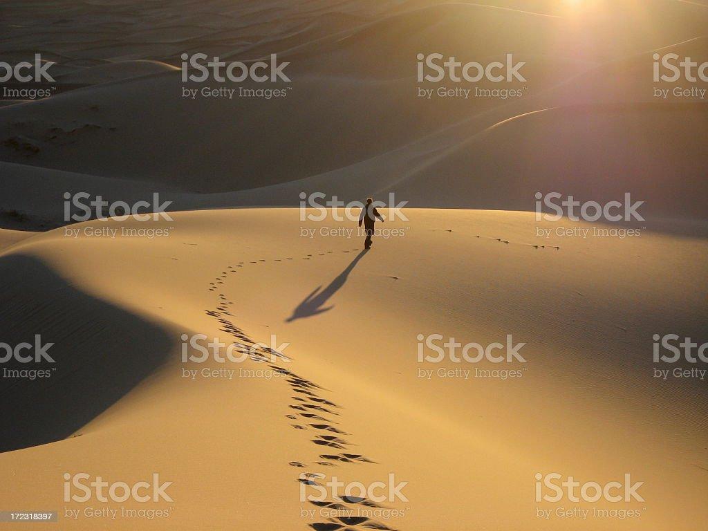 Man walking dunes at sunrise stock photo